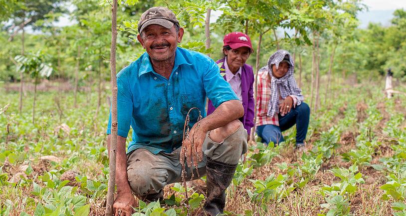 Nicaraguanische Familie kniet vor gepflanzten Bäumen